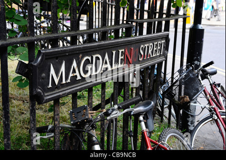 Bicycles parked against a fence in Magdalen Street, Oxford. - Stock Photo