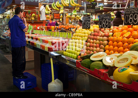 Man selling fresh fruit in stand at the La Boqueria market in Barcelona, Spain - Stock Photo