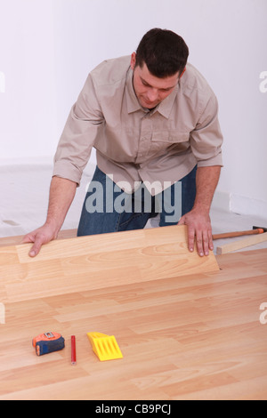 Man installing laminate flooring - Stock Photo