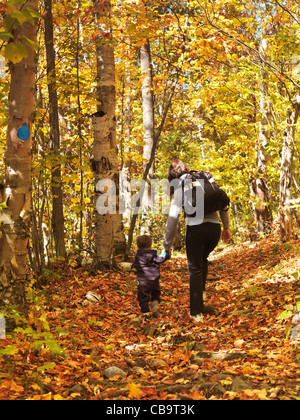 Woman with a child walking along a hiking trail in fall nature scenery. Killarney Provincial Park, Ontario, Canada - Stock Photo