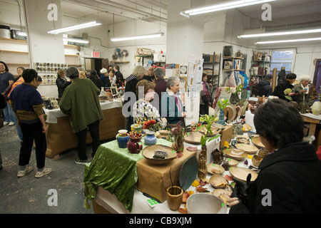 Members of a pottery studio in New York hold a holiday sale prior to Christmas - Stock Photo