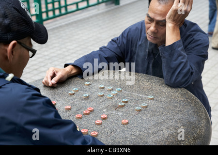 two chinese men playing xiangqi chinese chess on an outdoor board in a park hong kong hksar china - Stock Photo