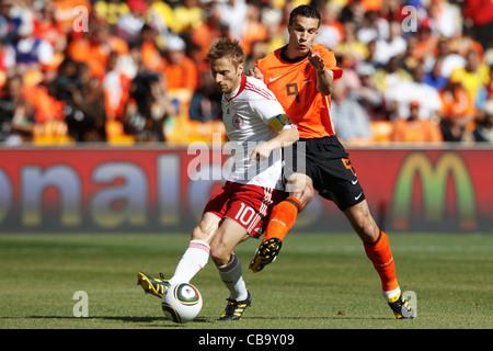 Robin van Persie of the Netherlands (R) pressures Denmark team captain Martin Jorgensen (L) during a 2010 World - Stock Photo