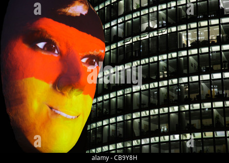 Huge sculpture of a face illuminated by an image of a German flag painted face during the festival of lights 2011 - Stock Photo