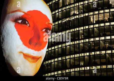 Huge sculpture of a face illuminated by an image of a Japanese flag painted face during the festival of lights 2011 - Stock Photo