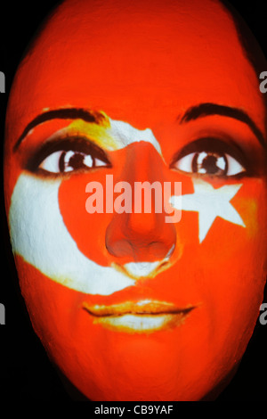 Huge sculpture of a face illuminated by an image of a Turkish flag painted face during the festival of lights 2011 - Stock Photo