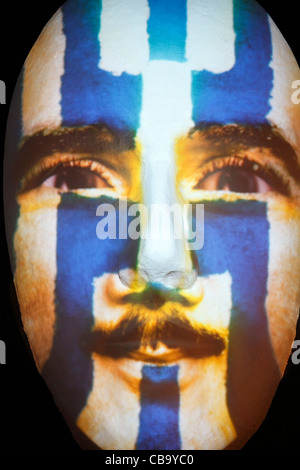 Huge sculpture of a face illuminated by an image of a Grecian flag painted man during the festival of lights 2011 - Stock Photo