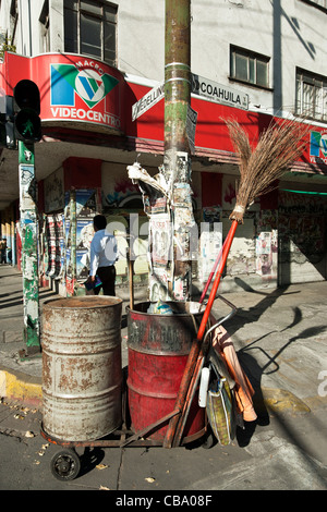 street cleaners cart with primitive twig broom parked on streetcorner plastered with advertising signs Roma district - Stock Photo