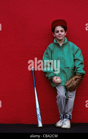Young boy standing in front of red wall getting his portrait taken holding a baseball and mitt - Stock Photo