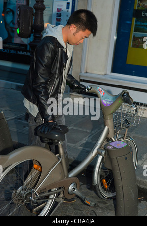 Paris, France, Young Chinese Man Using Free Velib Bicycle, Cycling at Night - Stock Photo