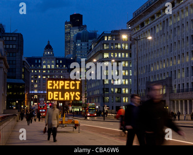 View along King William Street from London Bridge of workers walking home at nightfall; Expect delays electronic - Stock Photo