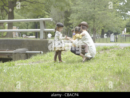 Mother and daughters playing in a park - Stock Photo