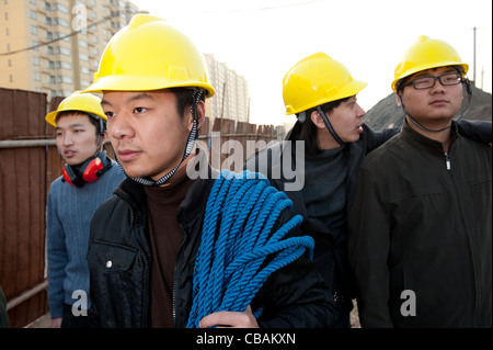 Construction workers walking and chatting at a construction site - Stock Photo