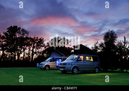 A VW Califonia and a Mazda Bongo camper van side by side on a campsite at sunset - Stock Photo