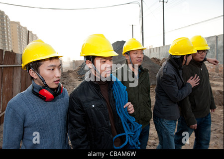 Construction workers walking at a construction site - Stock Photo