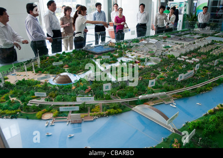 A hostess explains to the visitors the project of the China Solar Valley. Dezhou, Shandong, China - Stock Photo