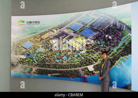 A hostess in front of the big billboard with the project of the China Solar Valley. Dezhou, Shandong, China - Stock Photo