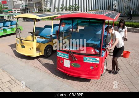 Two hostess set up a solar powered bus. China Solar Valley, Dezhou, Shandong, China - Stock Photo
