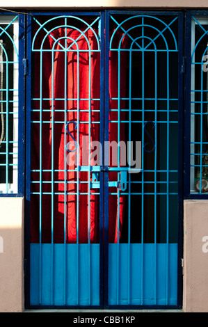 Colourful Blue Indian village gated house with red curtain. Andhra Pradesh. India