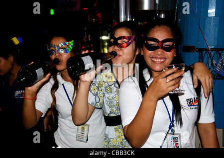 Thirsty Cambodian barmaids, wearing masquerade masks, celebrate new years eve at Sharky Bar, Phnom Penh, Cambodia. - Stock Photo