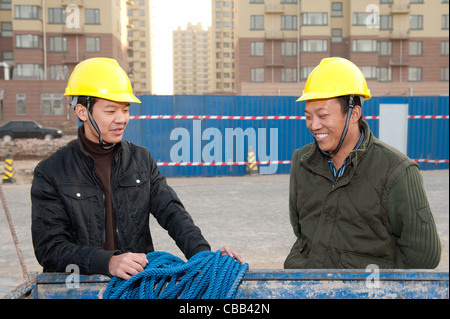 Construction workers chatting while at work - Stock Photo