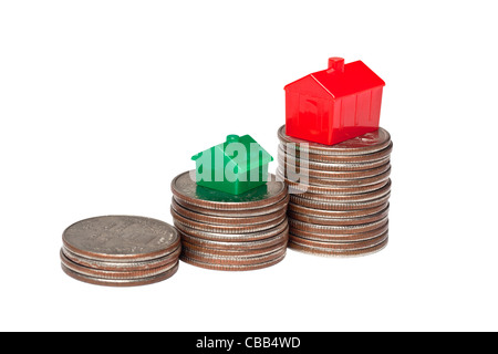Toys houses and pile of coins representing upgrade to a larger home - Stock Photo