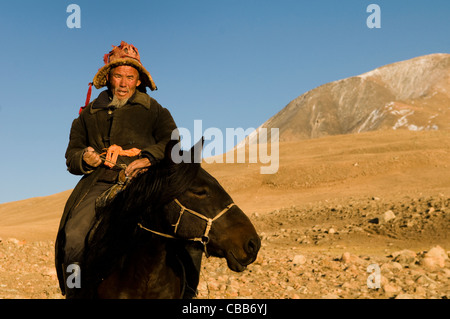 An old Kazakh eagle hunter on his horse in the Altai region of western Mongolia. - Stock Photo