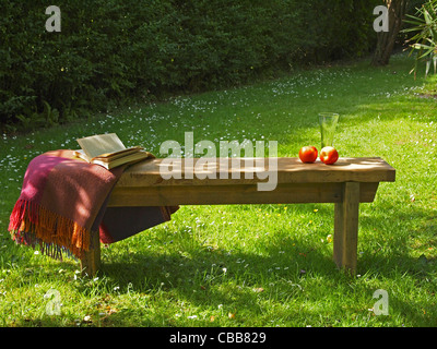 A relaxed atmosphere in a sunny English country garden - the wooden bench has a book, blanket and refreshments on - Stock Photo