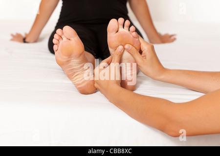 Human hands massaging a woman's foot - Stock Photo