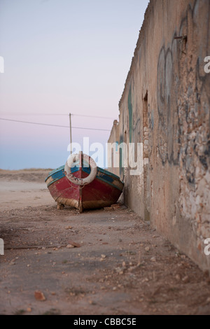 An old fishing boat laying next to a derelict building - Stock Photo