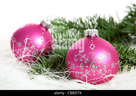 Two pink christmas balls with silver glitters over white background - Stock Photo