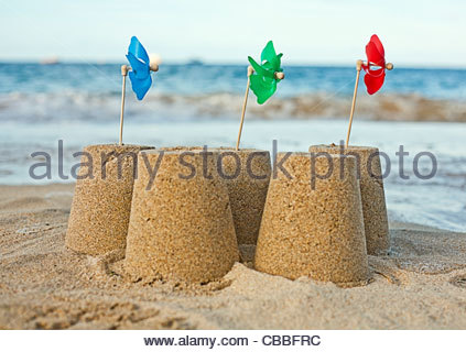 Sandcastles with pinwheels on beach - Stock Photo