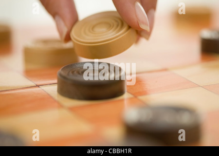Close up of woman playing checkers - Stock Photo