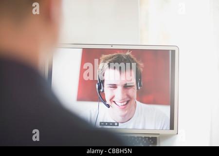 Teenagers talking on laptop - Stock Photo