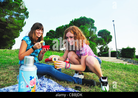 Teenage girls picnicking in rural field - Stock Photo