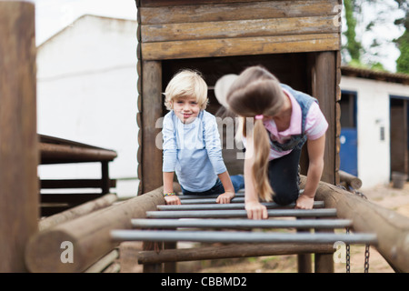 Children playing on monkey bars - Stock Photo