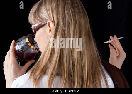 young girl smoking cigarette and drinking red wine - Stock Photo