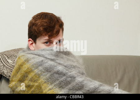 Man wrapped in blanket on couch - Stock Photo