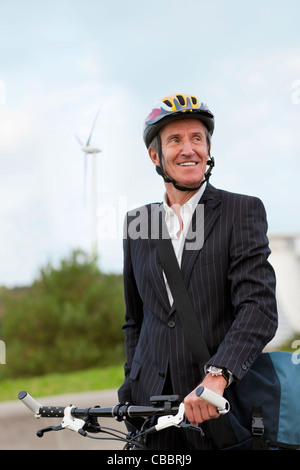 Businessman riding bicycle in urban park - Stock Photo