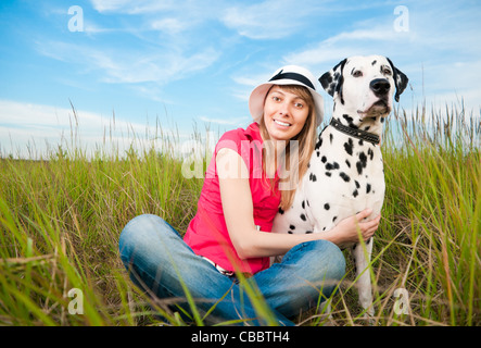beautiful young woman in hat sitting in grass with her dalmatian dog pet, smiling and looking into the camera - Stock Photo
