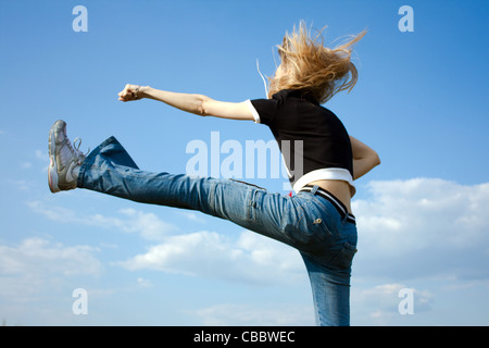 girl jumping outside with blue sky in background - Stock Photo