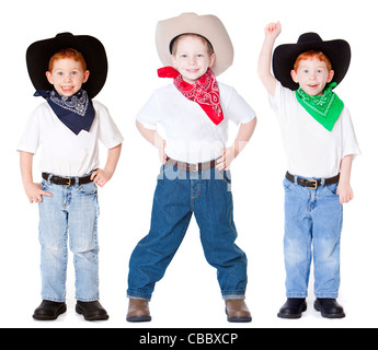 Three boys dressed up as cowboys in studio - Stock Photo