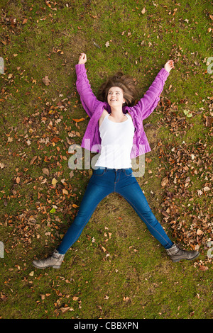 Teenage girl laying in grass in park - Stock Photo