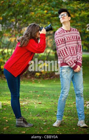 Teenage girl taking picture of boyfriend - Stock Photo
