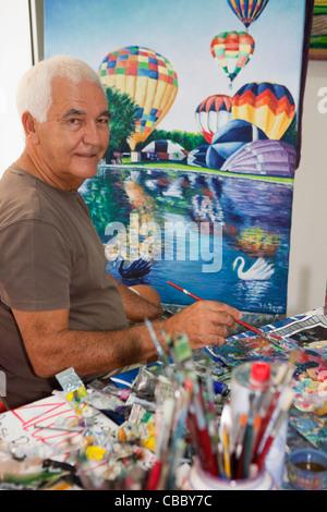 Older artist painting in studio - Stock Photo