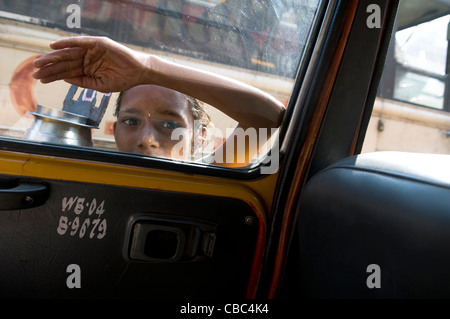A young beggar knocking on window and taxis on a busy street in Kolkata. - Stock Photo