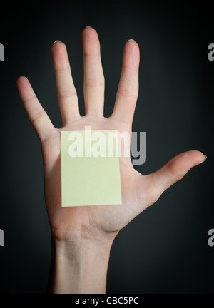 female hand with sticky office note on dark background . Note is blank and yellow - Stock Photo
