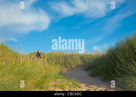 Woman walking in long grass - Stock Photo