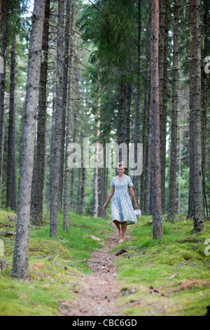 Woman walking on path in forest - Stock Photo