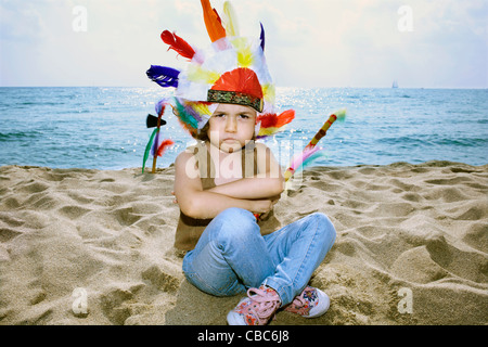 Toddler in Indian headdress on beach - Stock Photo